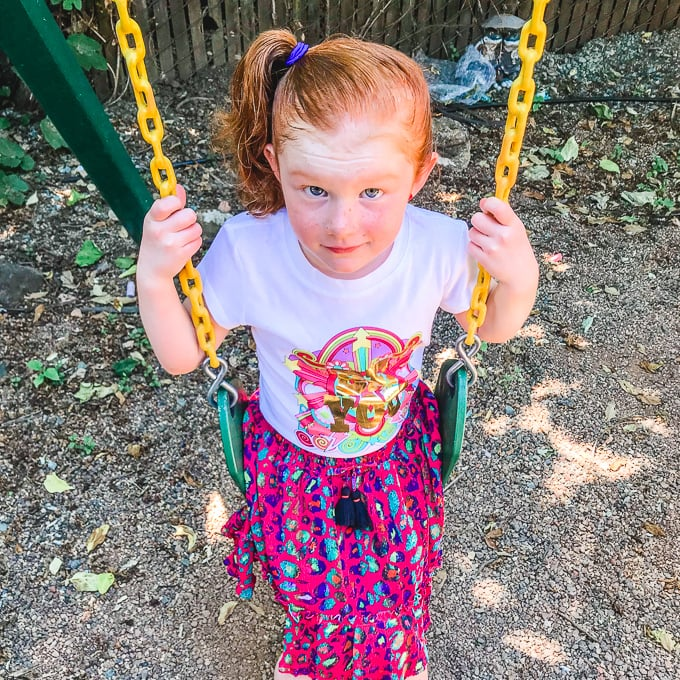 Red-headed girl on swing in purple skirt and white shirt.
