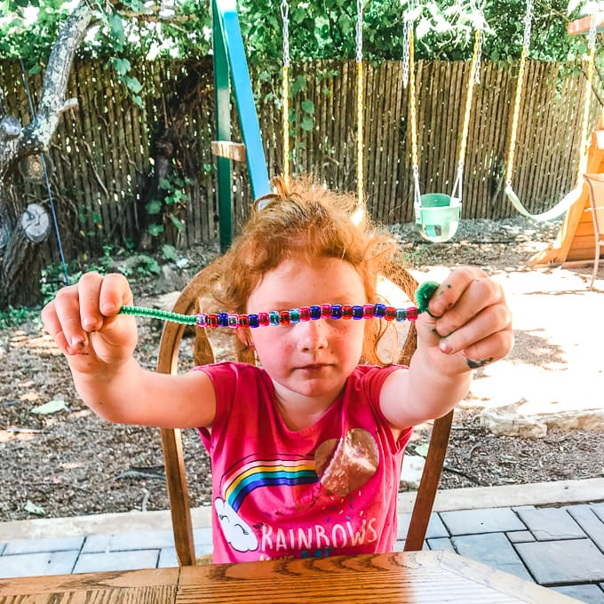 A little girl holding up a pattern snake made from colorful beads and a pipe cleaner.
