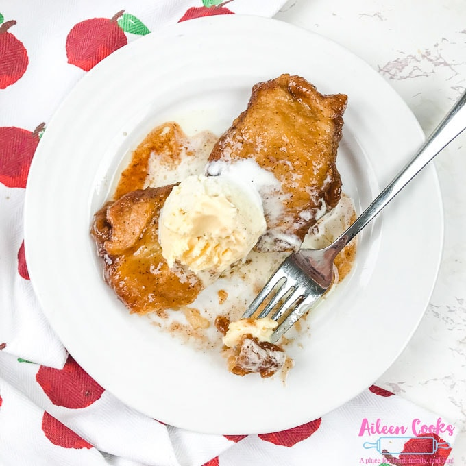 A white plate with two apple dumplings topped with vanilla ice cream.