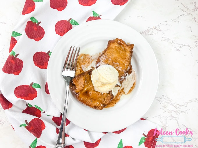 A plate of two instant pot apple dumplings under a scoop of vanilla ice cream.