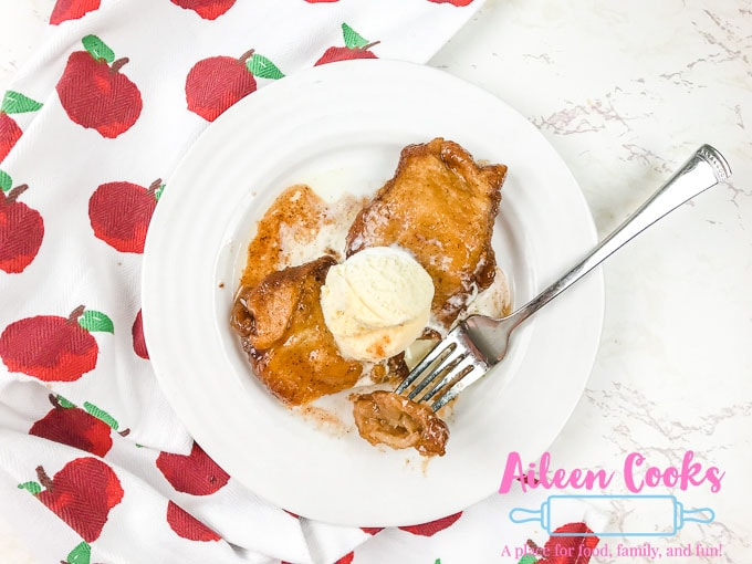 A plate of instant pot apple dumplings with a bite on a fork.