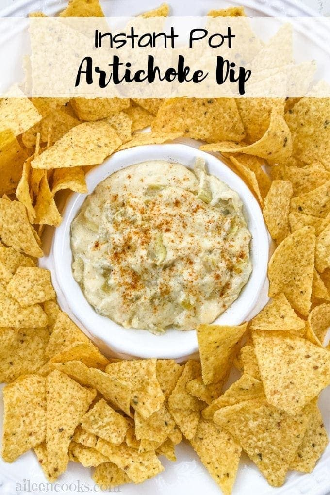 A bowl of instant pot artichoke dip surround by tortilla chips.
