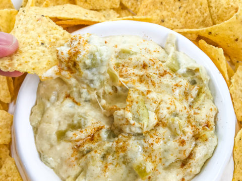 A hand holding a chip with instant pot artichoke dip on top.