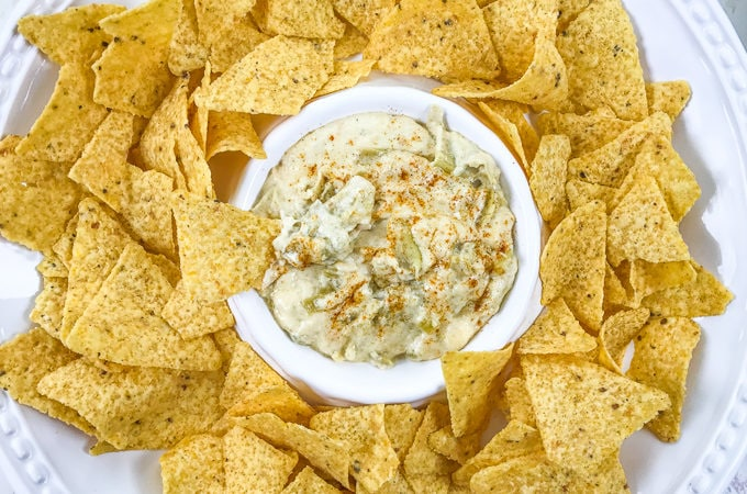 A bowl of instant pot artichoke dip with a chip sticking out of the top of the bowl.
