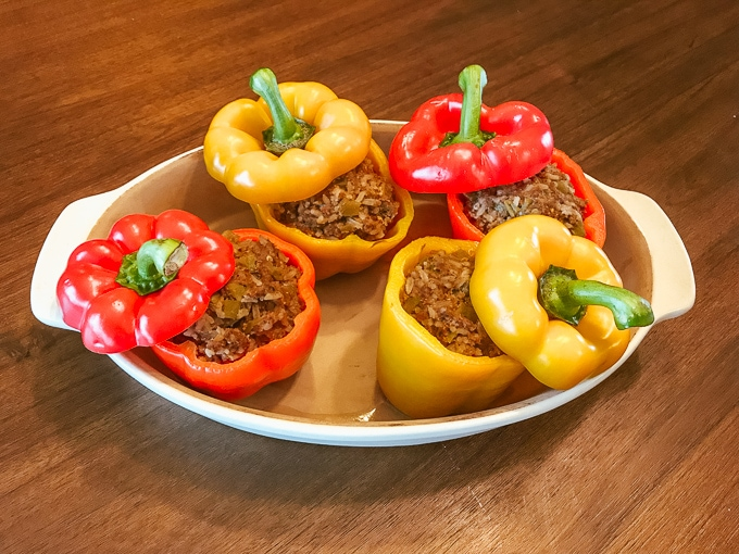 A dish filled with four instant pot taco stuffed peppers.
