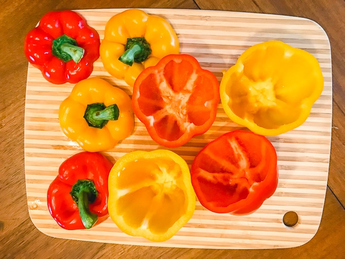 Red and yellow bell peppers with the tops sliced off.