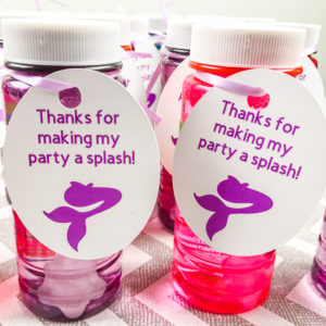 Two bottles of bubbles with mermaid favor tags tied on with purple ribbon.