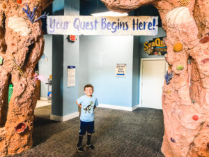 "A boy posing in front of a sign that says ""Your Adventure Starts Here""."