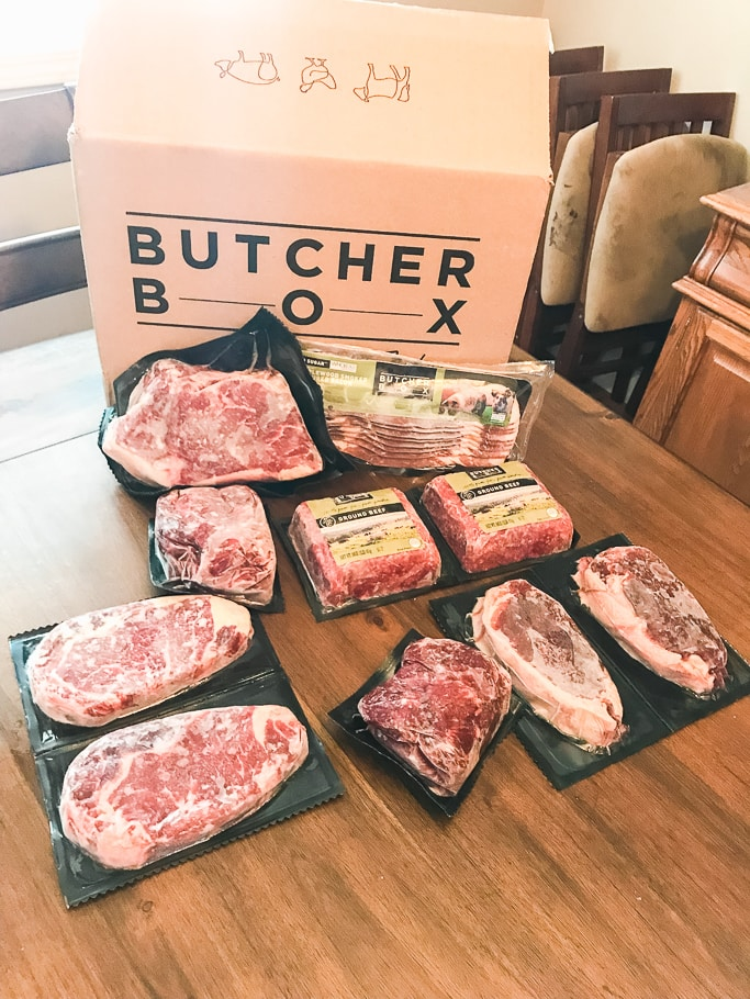 Butcher box with 9 cuts of meat on table next to a pound of bacon.