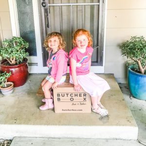 Two girls sitting on a Butcher Box delivery, on their front porch.