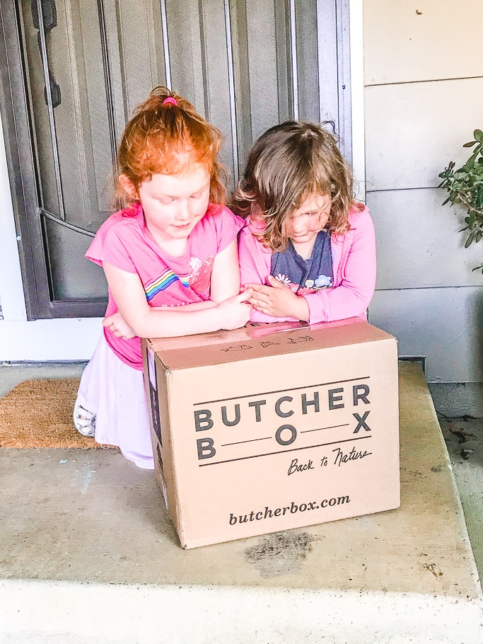 "Two girls leaning over a box with the words ""butcher box"" written on it."