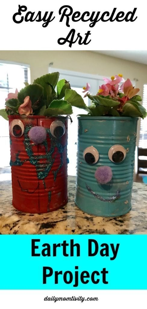 Two tin cans painted in red and blue with faces glued on the front, holding flowers.