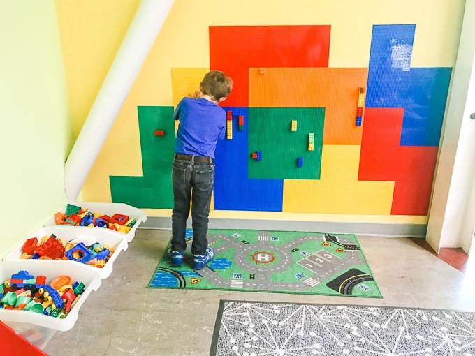 A boy building a creation on a LEGO wall.