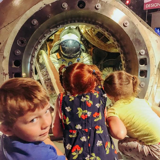 Three kids looking inside a Russian space module.