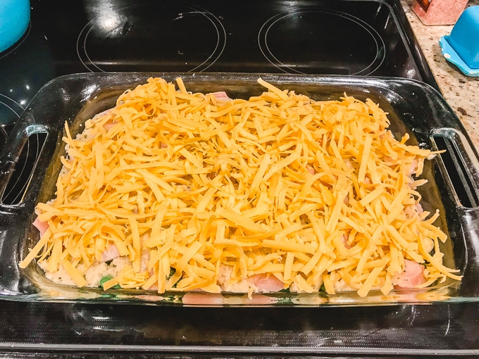 A casserole dish layered with red potatoes, green beans, chicken, béchamel sauce, and shredded cheese.