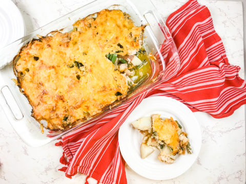 A plate of chicken and potato casserole next to the casserole dish.