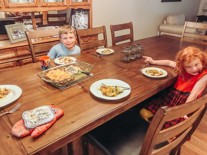 Two kids sitting a table eating cheesy ranch chicken and potato casserole.