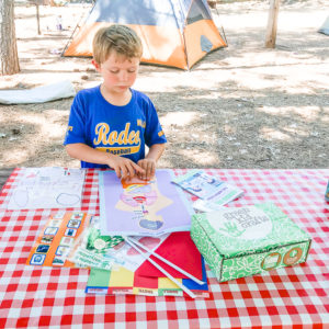 A boy working on the human body poster from the green kid crafts box.