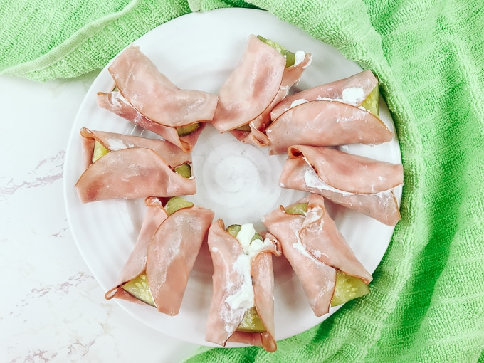 ham and cream cheese roll ups arranged in a circle on a white plate next to a green towel.