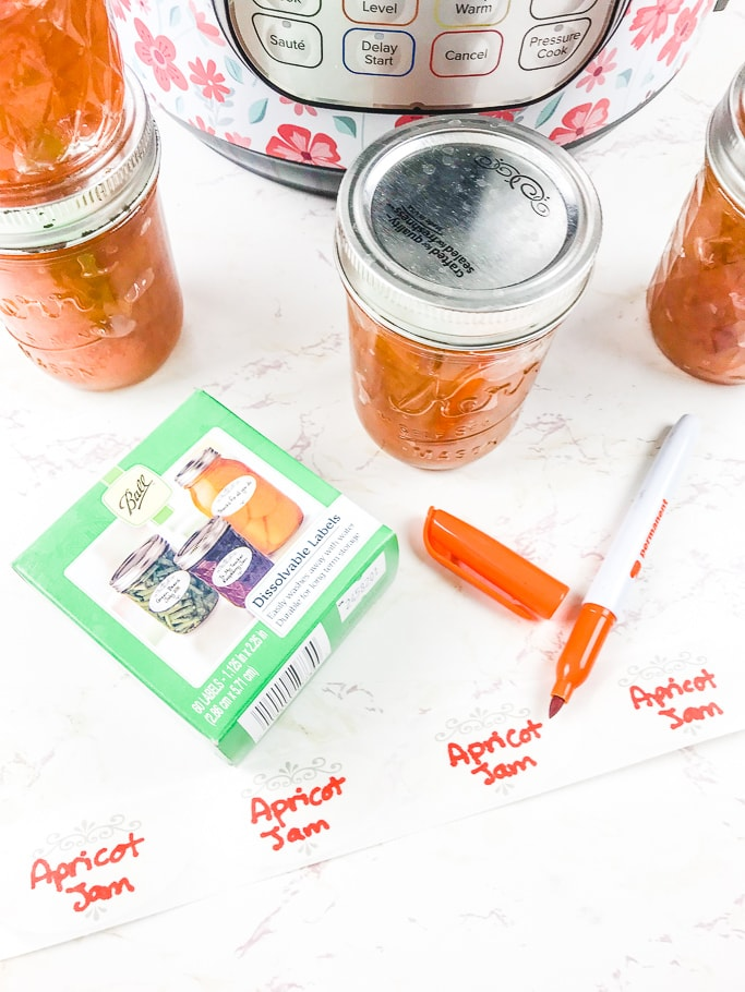 A jar of peach jam next to Ball Dissolvable labels and an orange permanent marker.