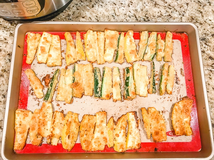 parmesan zucchini fries on a cookie sheet.