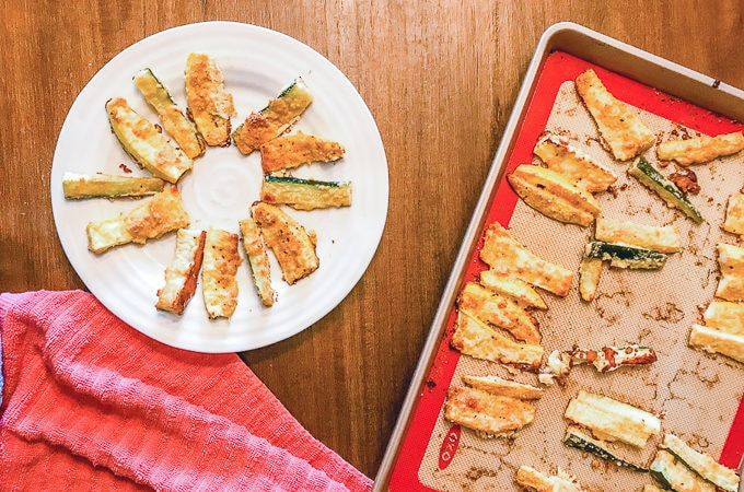 Parmesan zucchini fries arranged in a circle on a white plate next to a cookie sheet full of zucchini fries.