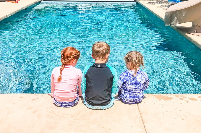 Three kids sitting at the edge of a pool with their back to the camera, in swimwear with spf.
