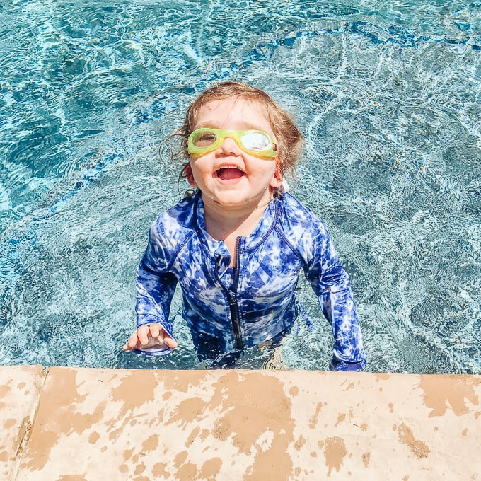 Toddler girl standing in shallow end of pool wearing goggles and toddler swimwear.