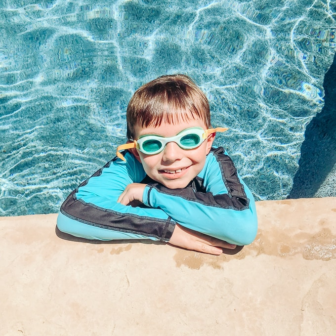 A boy in a pool, leaning over the edge and smiling.