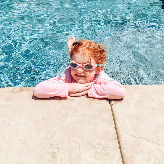 Girl in pink swimsuit leaning over the side of the pool and smiling.