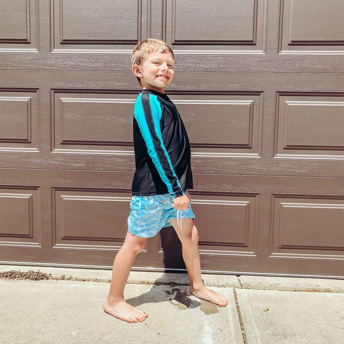 Young boy posing in swimwear with sun protection in front of brown garage door.