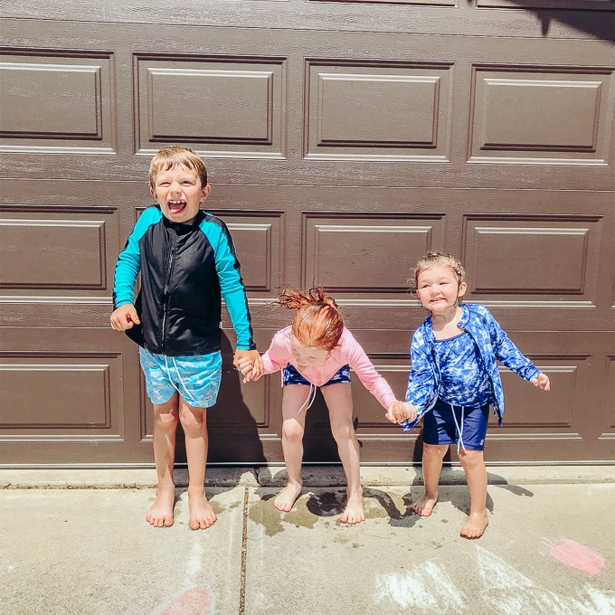 Three kids holding hands and swearing swimsuits from SwimZip in front of a brown garage door.