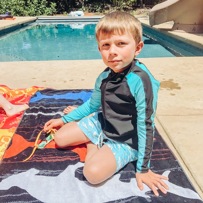 Boy sitting on a towel in front of a pool wearing a blue and black swimsuit with spf.