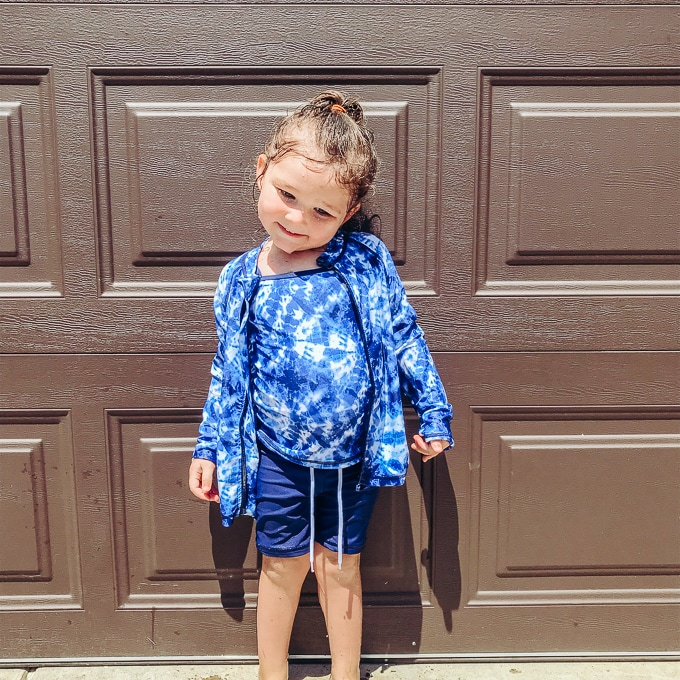 Toddler girl wearing blue swim shirt and shorts.