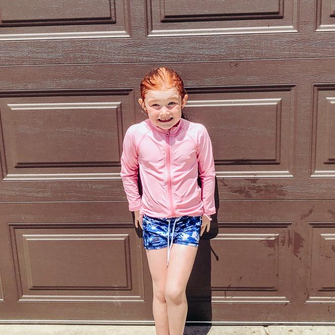 Girl in pink and blue swimsuit standing in front of brown garage door.