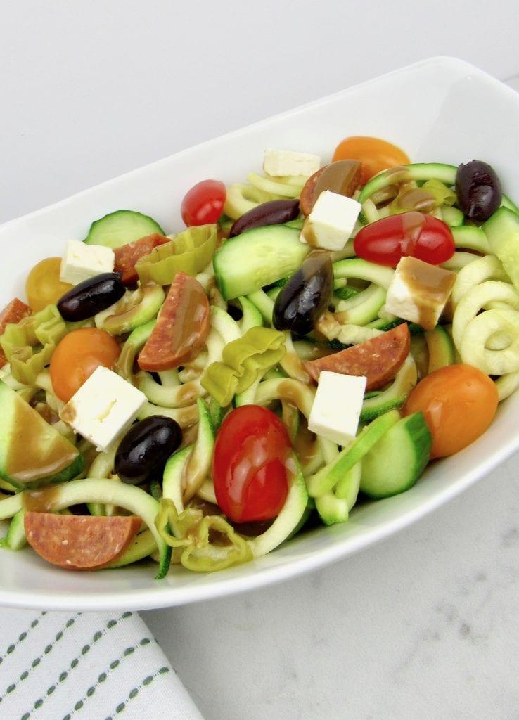 Zucchini pasta salad in a white oval bowl.