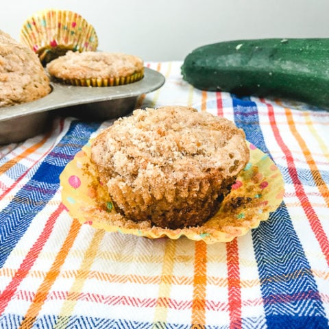 Chocolate Chip Zucchini Muffin with muffin cup partially pulled down.