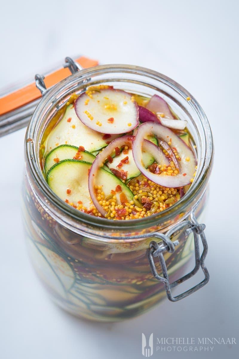 Pickled zucchini in a glass jar.