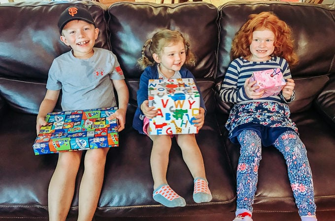 Three kids sitting on a black couch, holding their wrapped gifts.