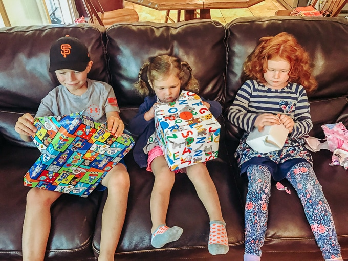Three kids opening their presents - gift ideas for kids.