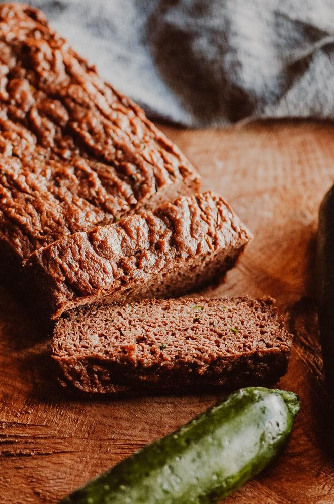 A loaf of gluten free zucchini bread sliced on a cutting board.