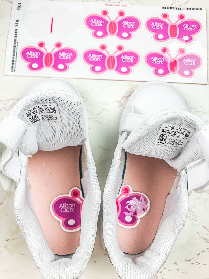 A pair of white sneakers with butterfly stickers inside.