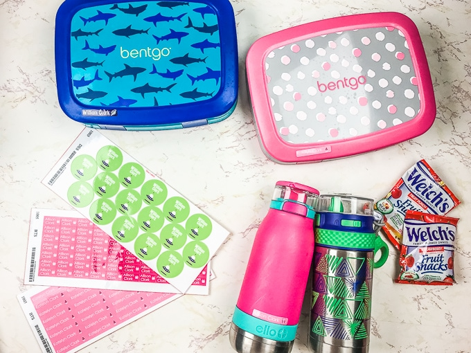An overhead shot of our favorite school lunch supplies, including bento box, water bottle, fruit snacks, labels.