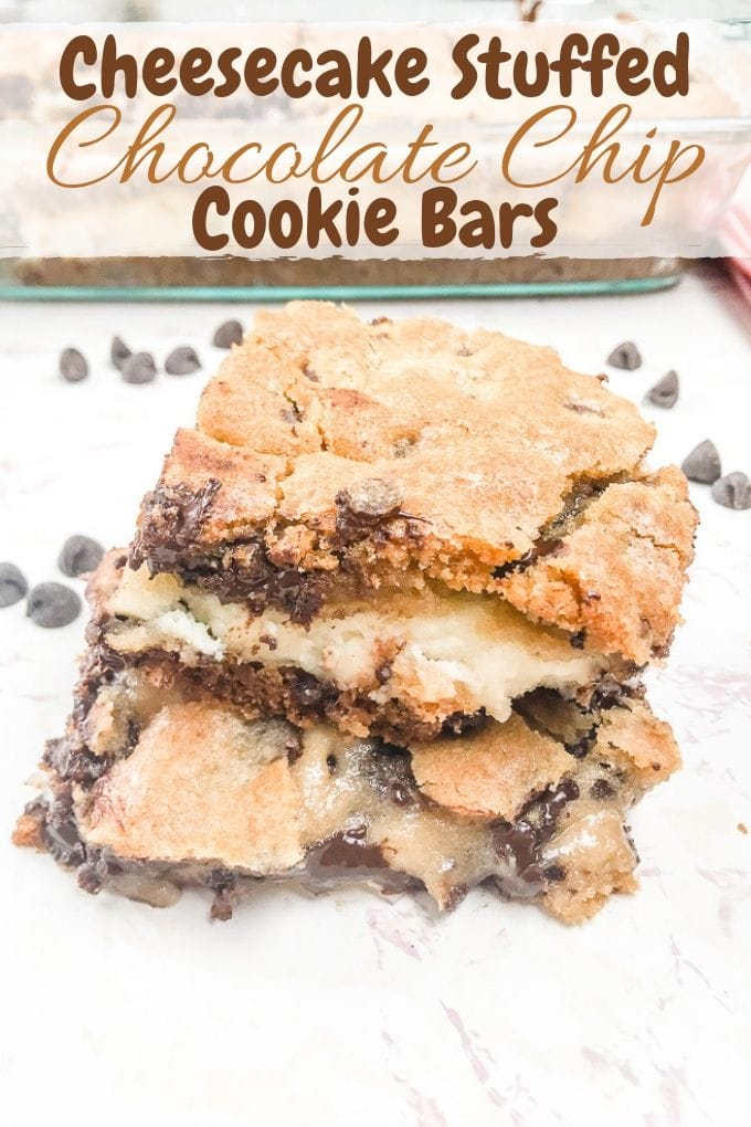 Two chocolate chip cookie cheesecake bars stacked top of each other.