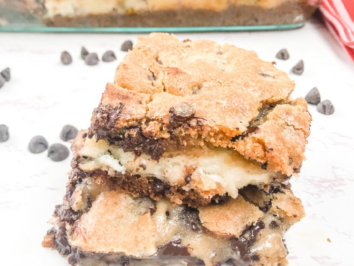 Two chocolate chip cookie cheesecake bars stacked up.