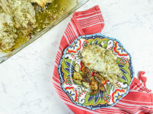 A glass casserole dish filled with creamy pesto chicken and next to a plate served with pesto chicken bake.