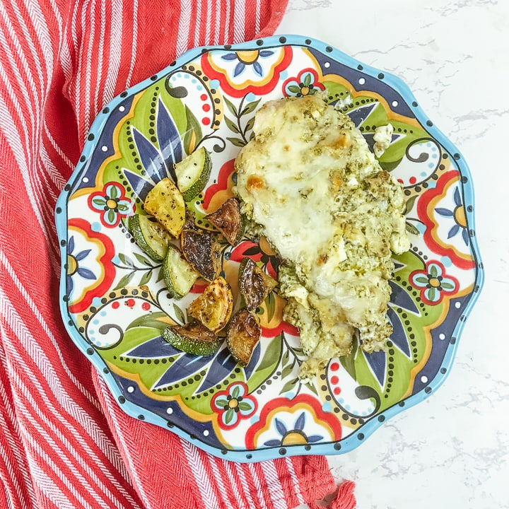A red striped towel under a colorful plate topped with creamy pesto chicken and roasted zucchini.