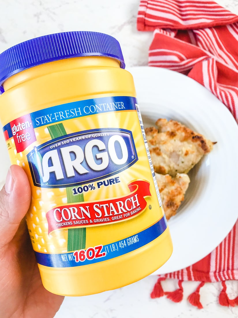 A hand holding up a container of Argo Corn Starch over a bowl of crispy oven baked chicken thighs.