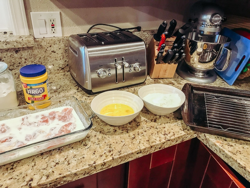 A photo of a kitchen counter set up to make crispy chicken thighs with bowls of egg and a bowl of crispy coating.