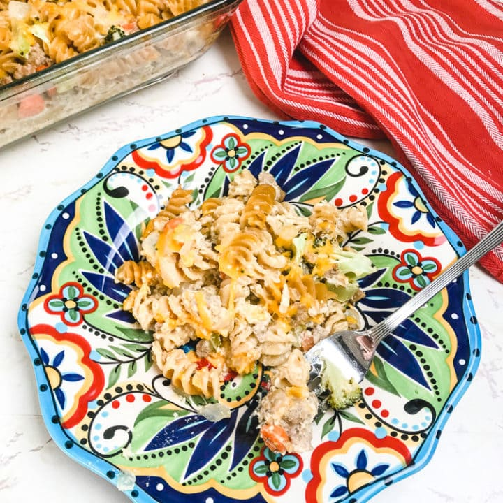 A bite of turkey noodle casserole on a colorful plate.
